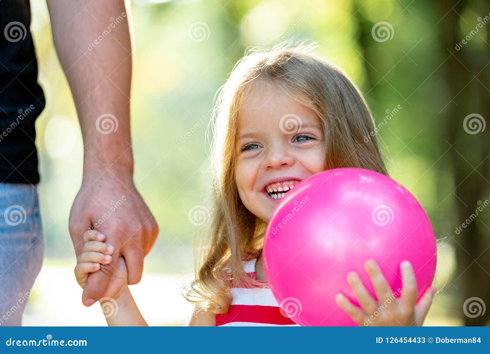 Familj, föräldraskap, faderskap, adoption och folkbegrepp - lycklig fader och liten flicka som går att rymma i hand in
