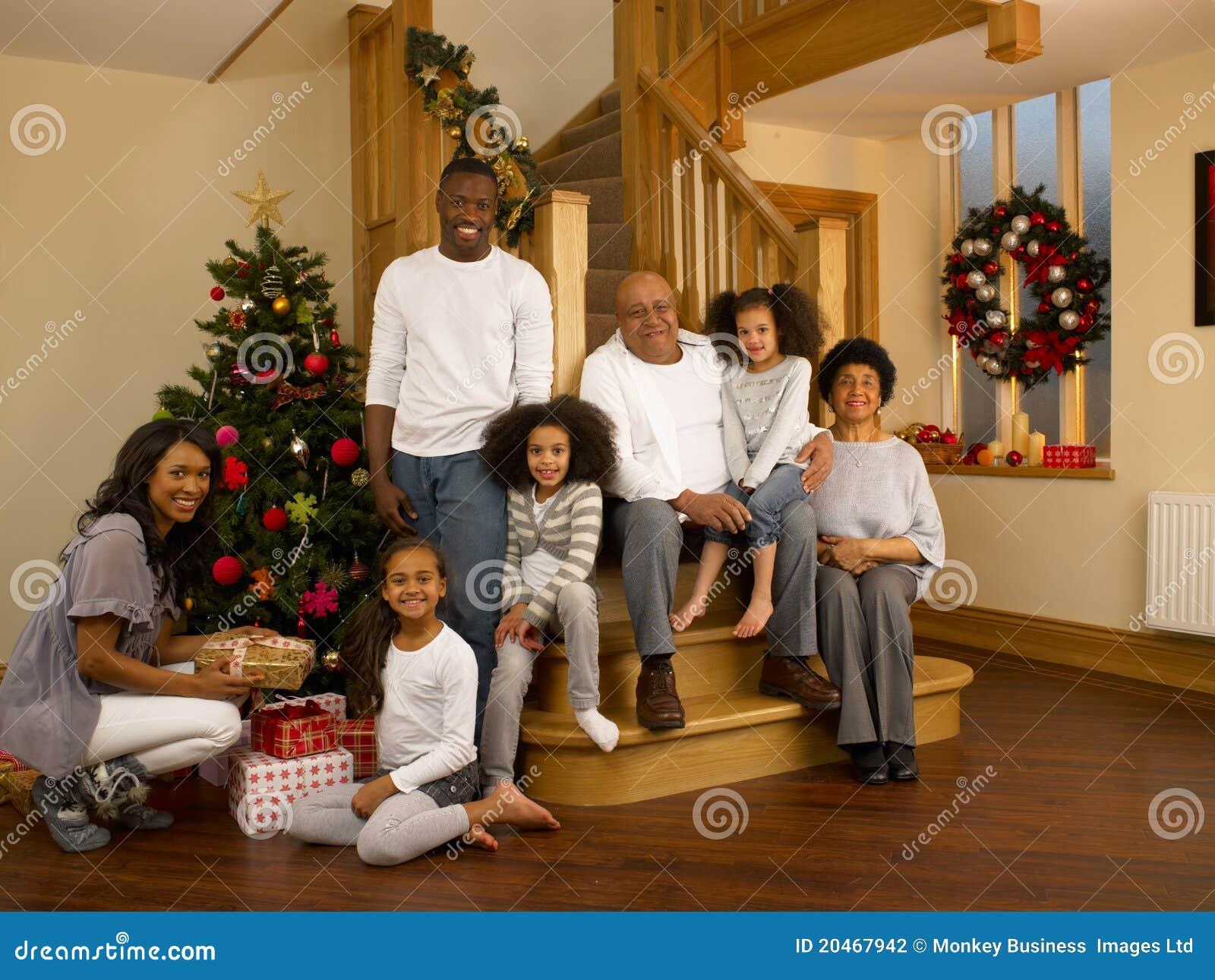 Familj för blandad race med julgranen och gåvor
