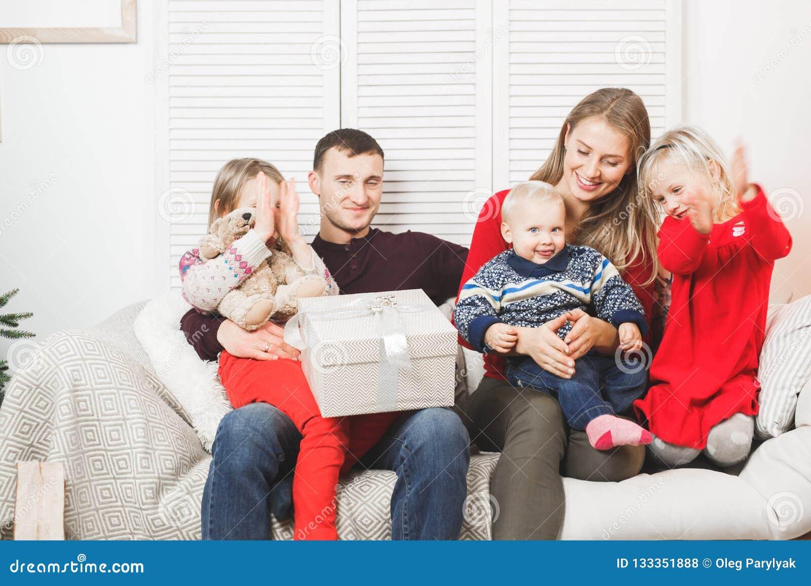Familj för lycklig jul med ungar som öppnar gåvan