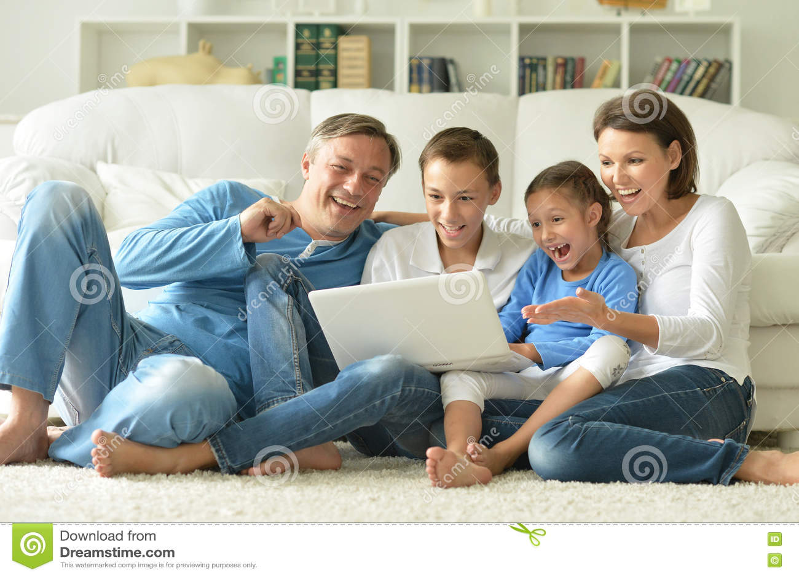 Familj hemma med bärbar dator