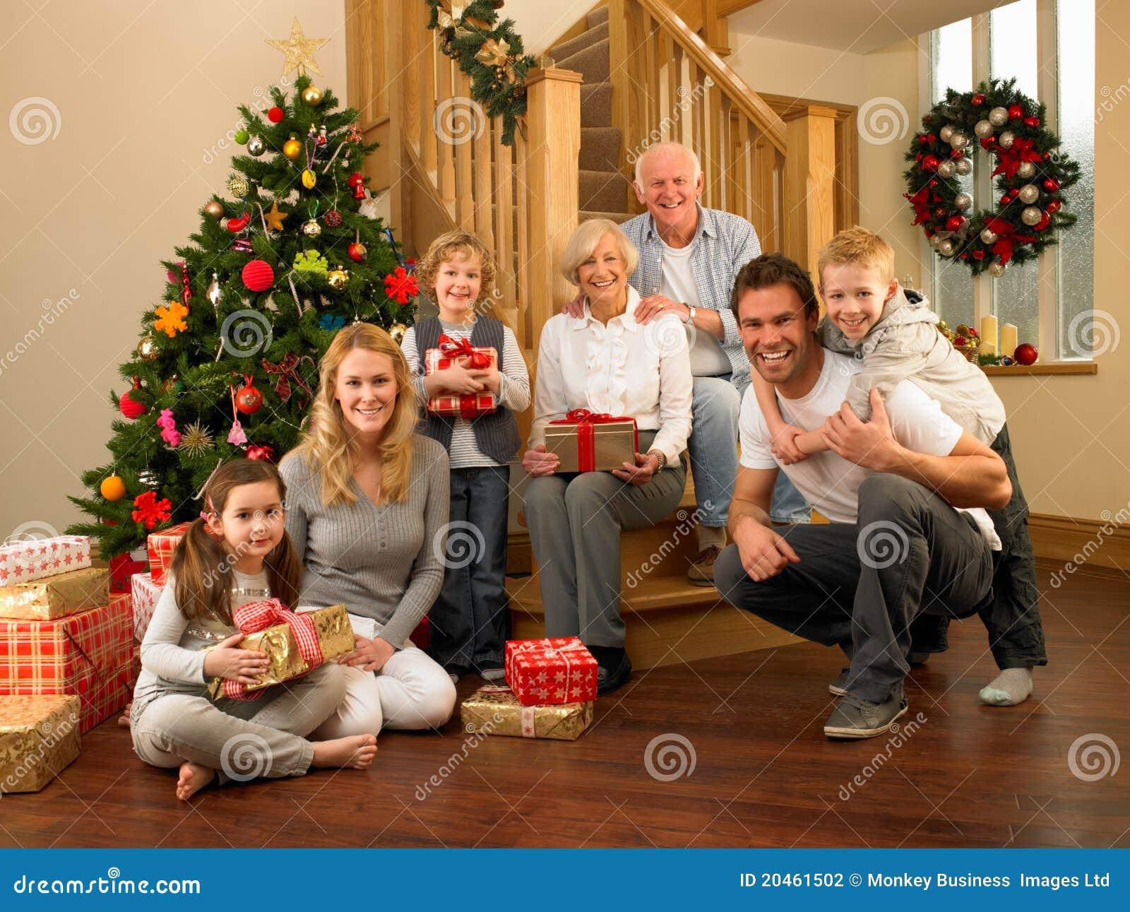 Familj hemma runt om jultree