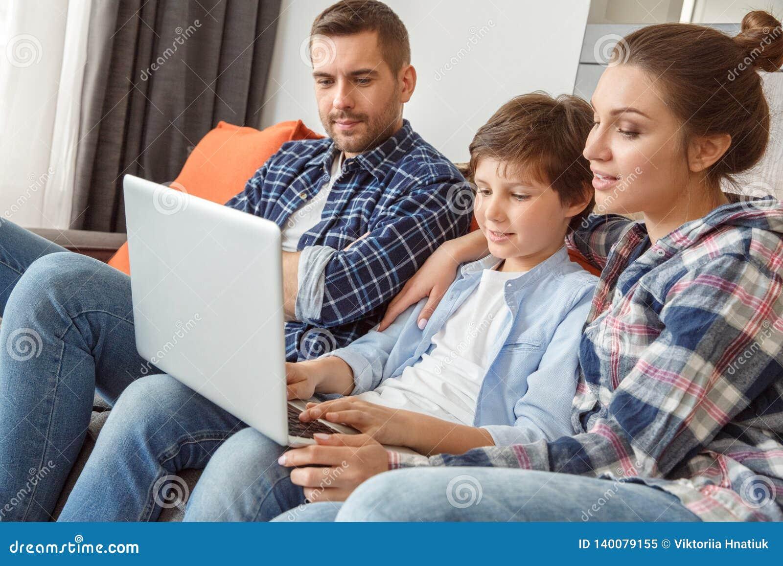 Familj hemma som sitter på soffan i vardagsrum som bläddrar tillsammans internet på den koncentrerade bärbara datorn