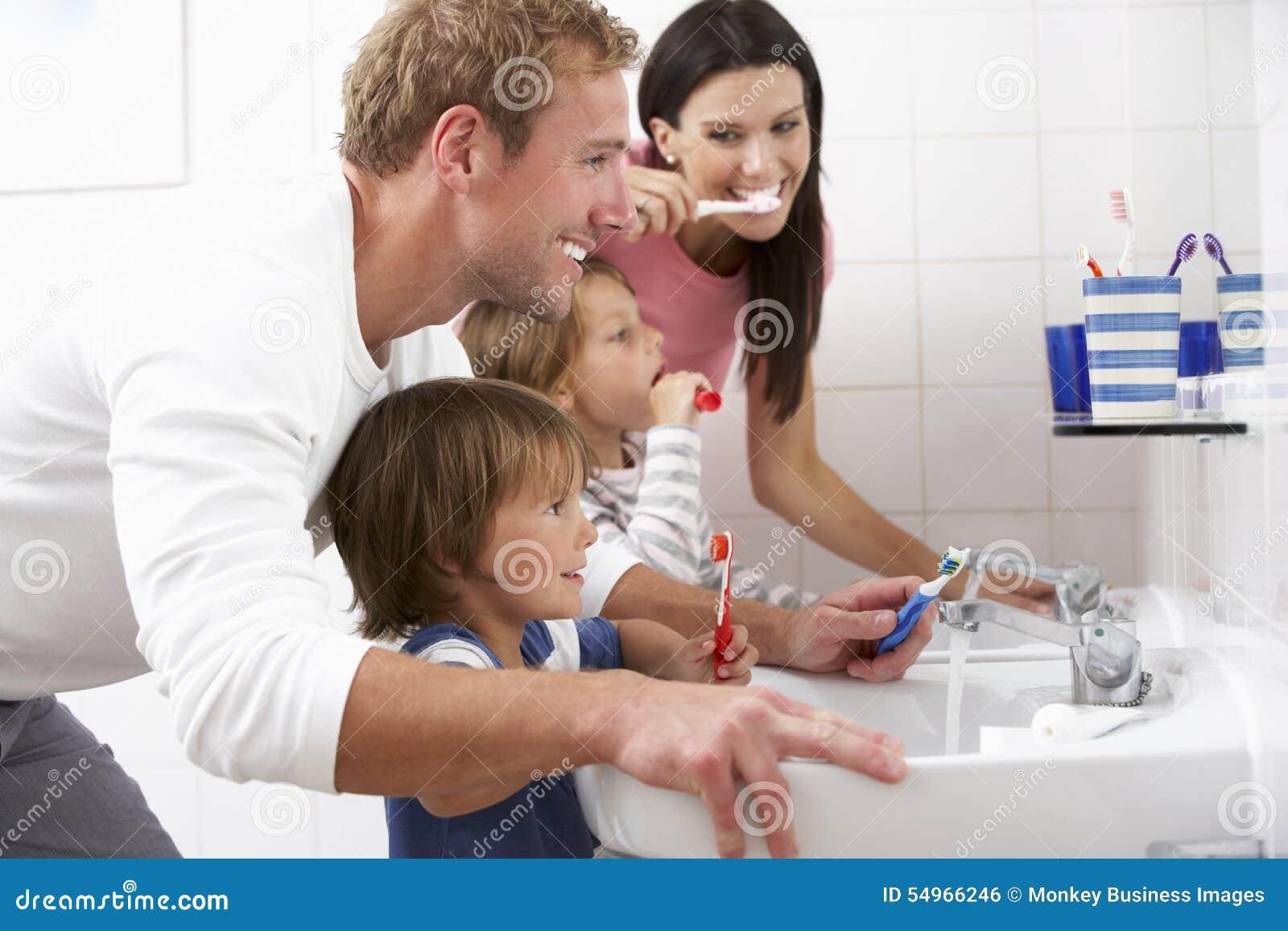 Familj i badrum som borstar tänder