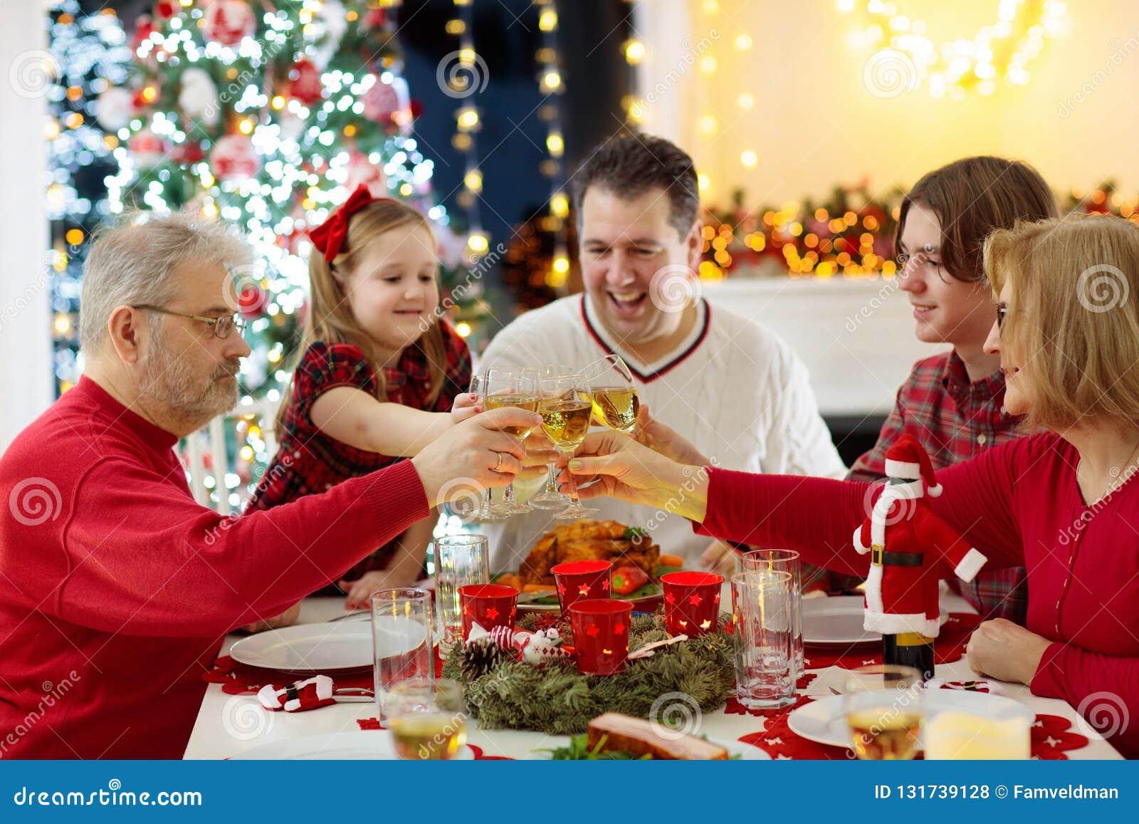 Familj med barn som äter julmatställen på spisen och det dekorerade Xmas-trädet Föräldrar, morföräldrar och ungar på festligt mål