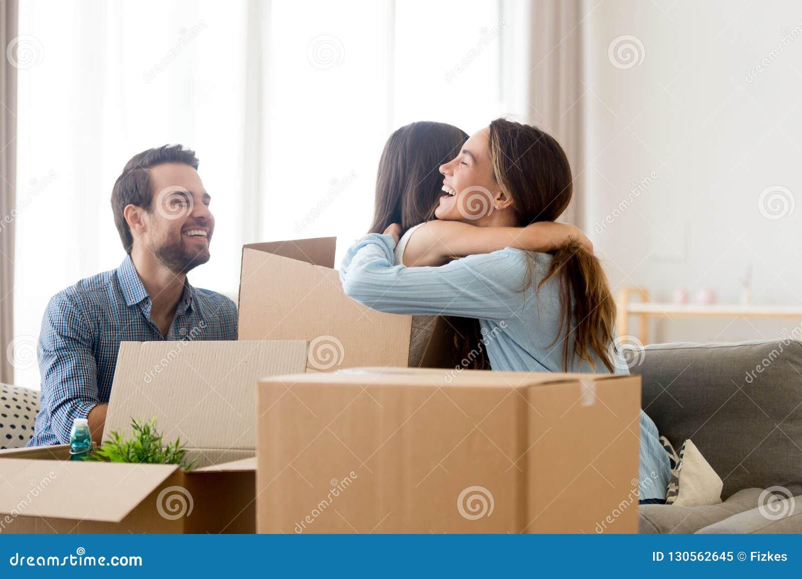 Familj med högen av lådaaskar i vardagsrum