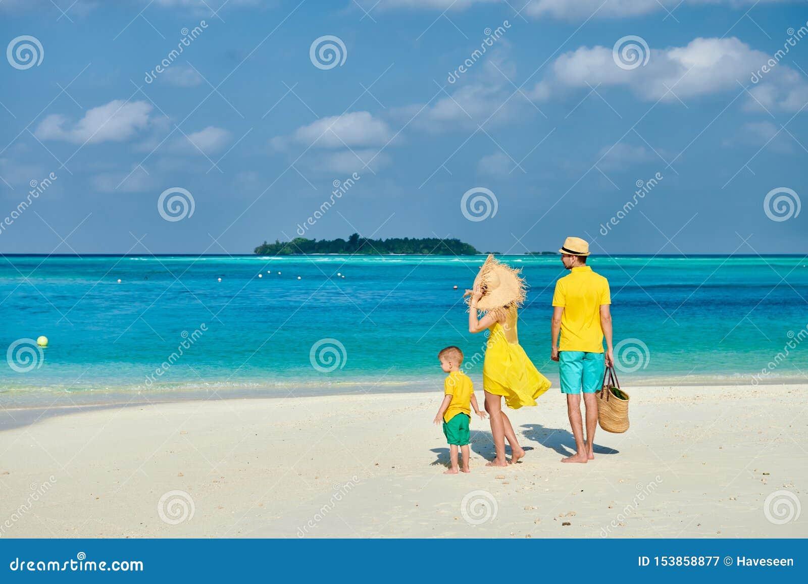 Familj med ?rig pojke tre p? stranden