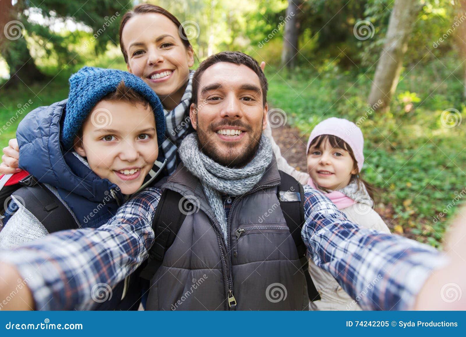 Familj med ryggsäckar som tar selfie och att fotvandra