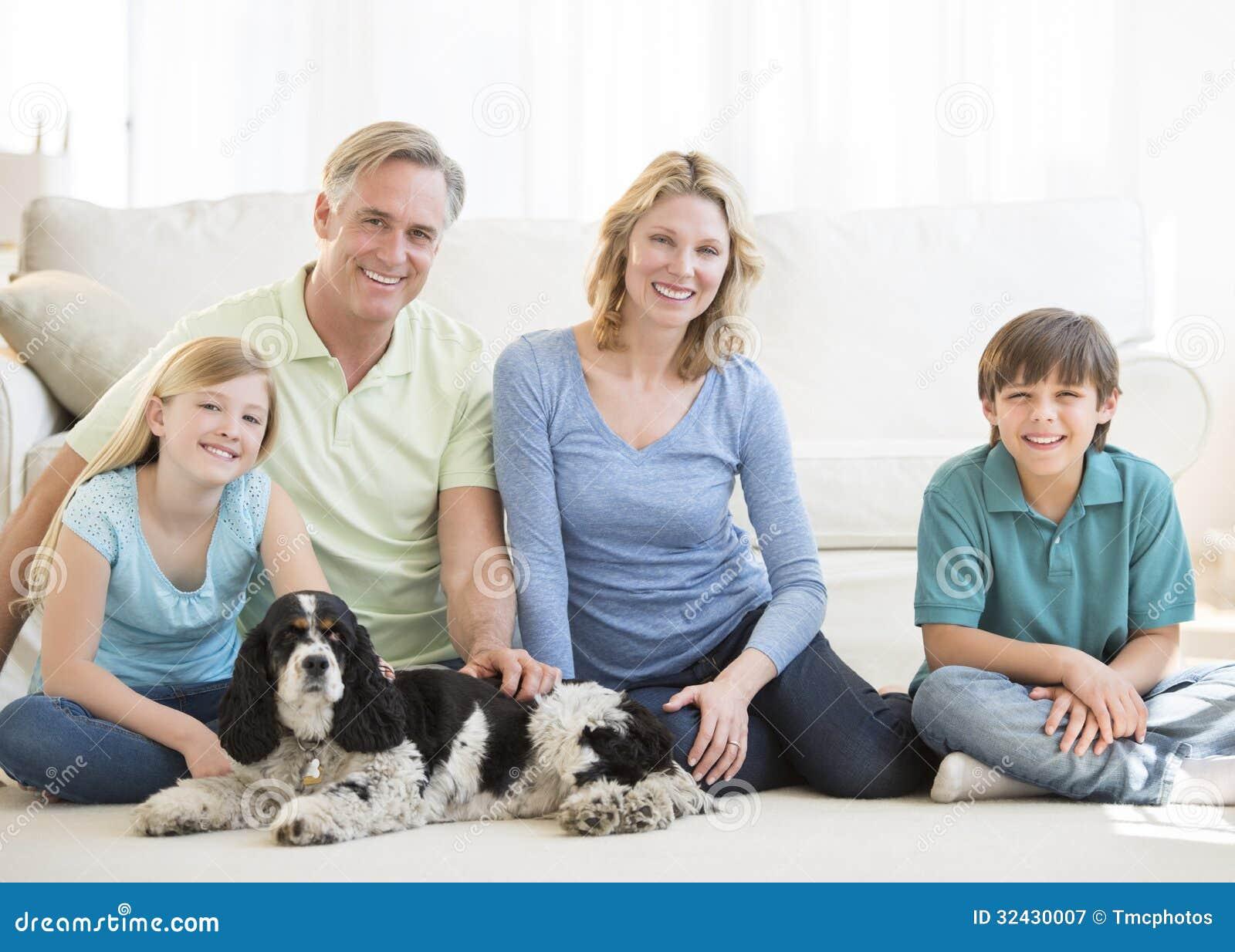Familj med sammanträde för älsklings- hund på golv i vardagsrum