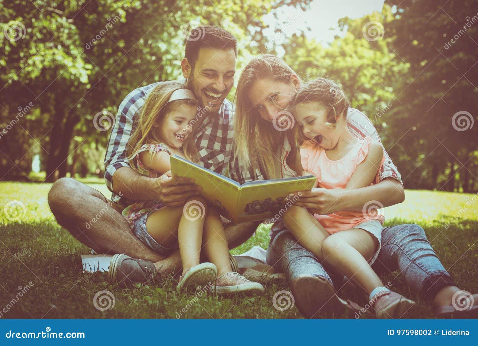 Familj med två barn i ängläsebok tillsammans
