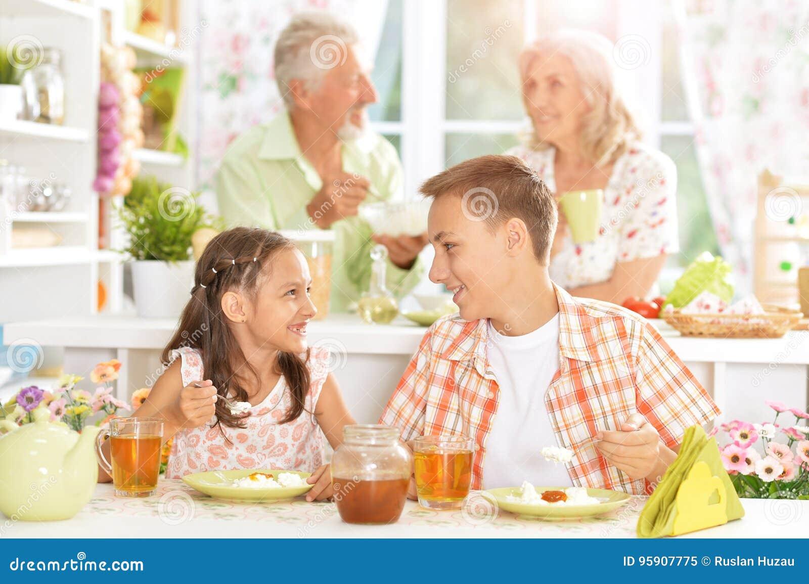Familj med ungar som har frukosten