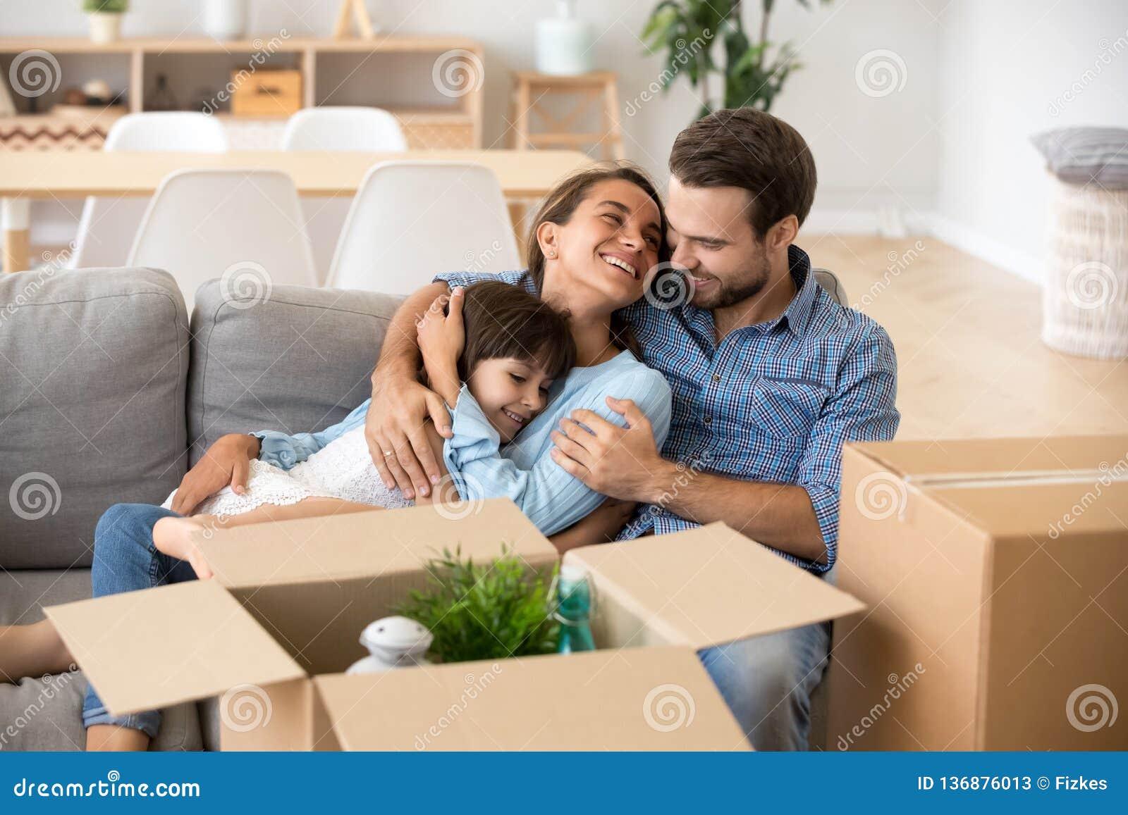 Familj med ungen som omfamnar på nytt hem för soffainflyttning