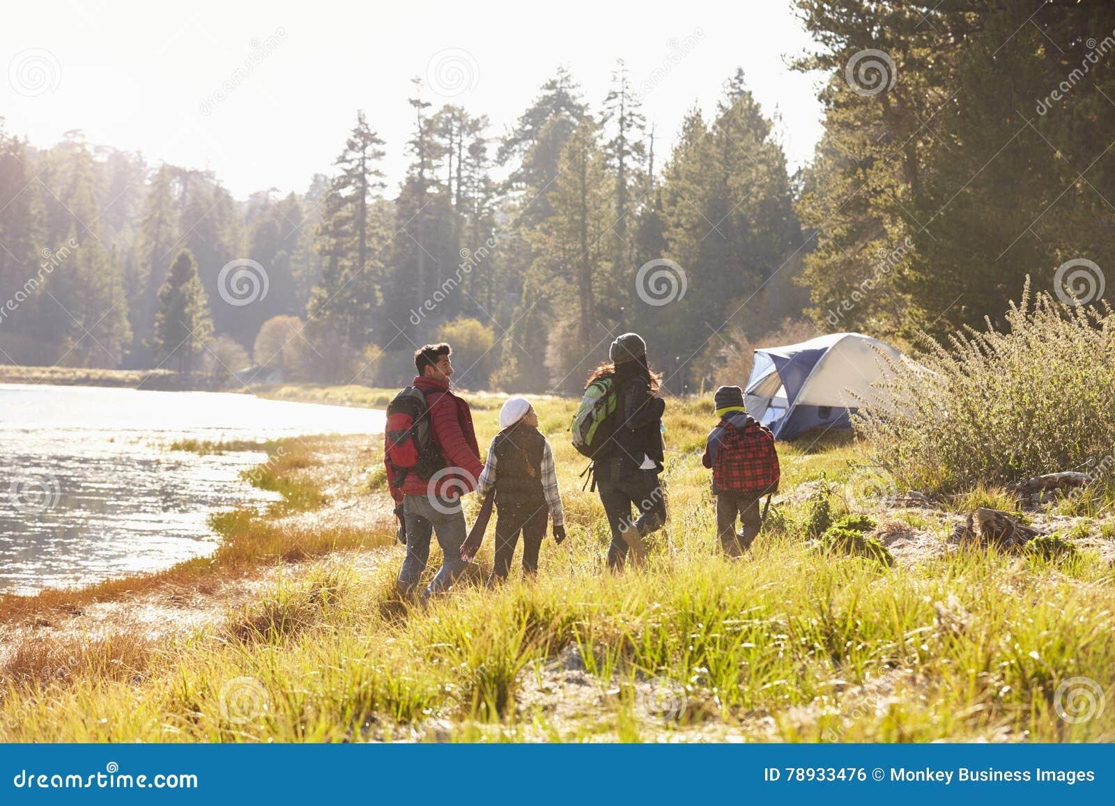 Familj på en campa tur som går nära en sjö, baksidasikt