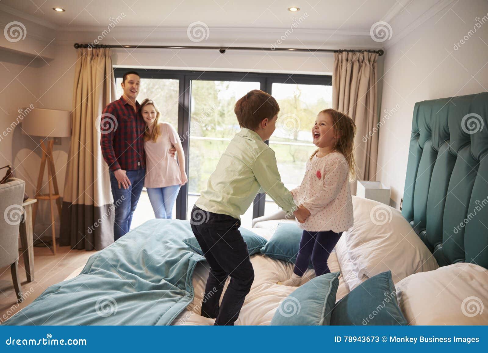 Familj på semester med barn som spelar på hotellsäng