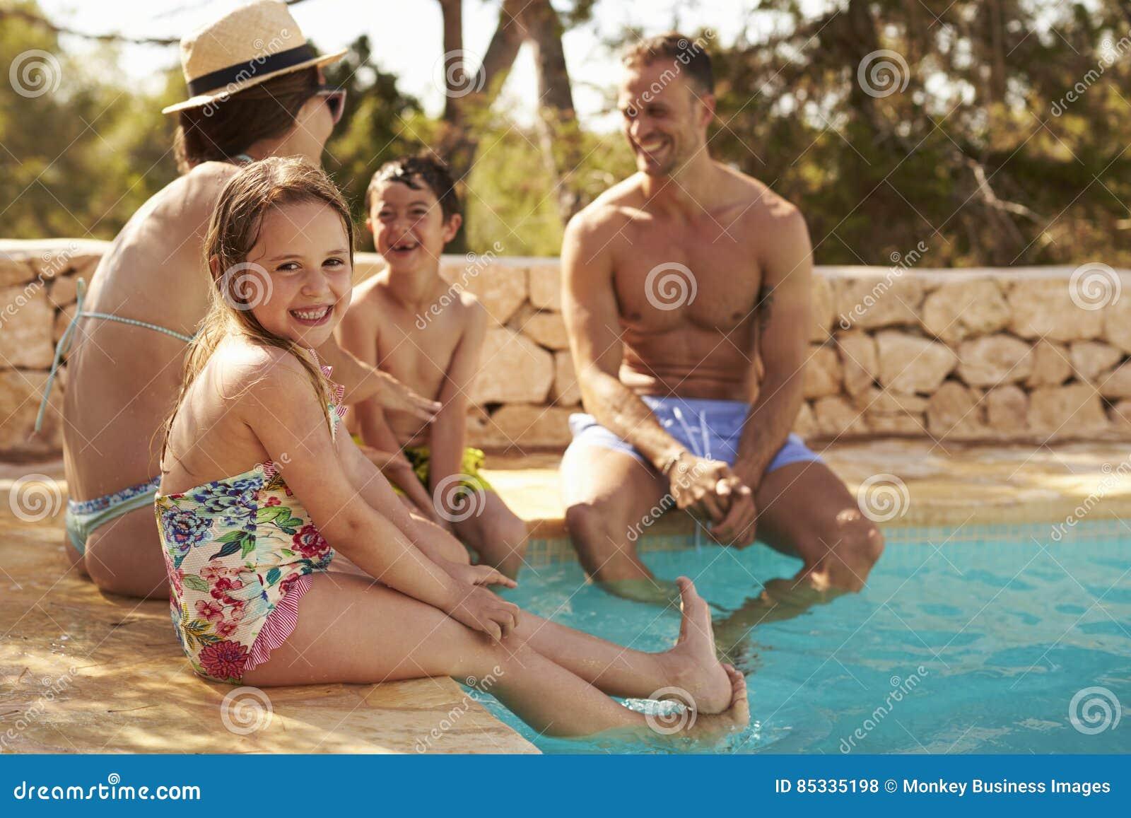 Familj på semester som kopplar av vid den utomhus- pölen