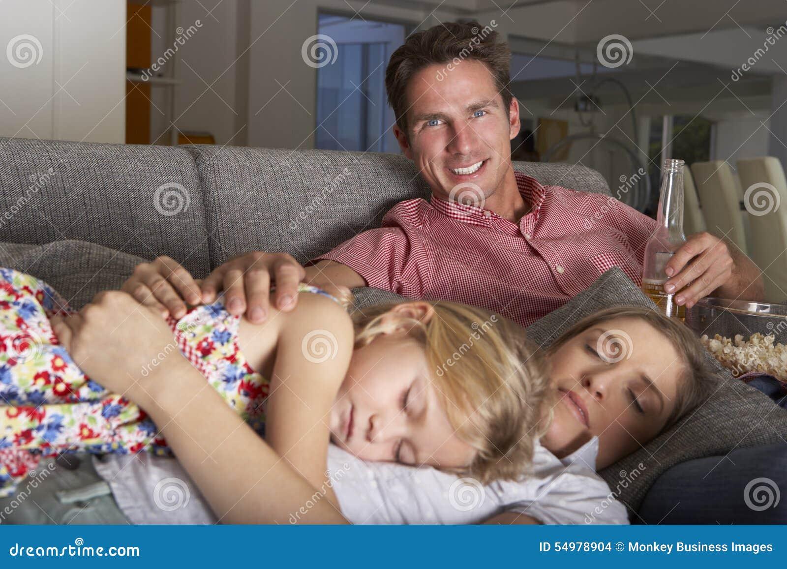 Familj på Sofa Watching TV och ätapopcorn