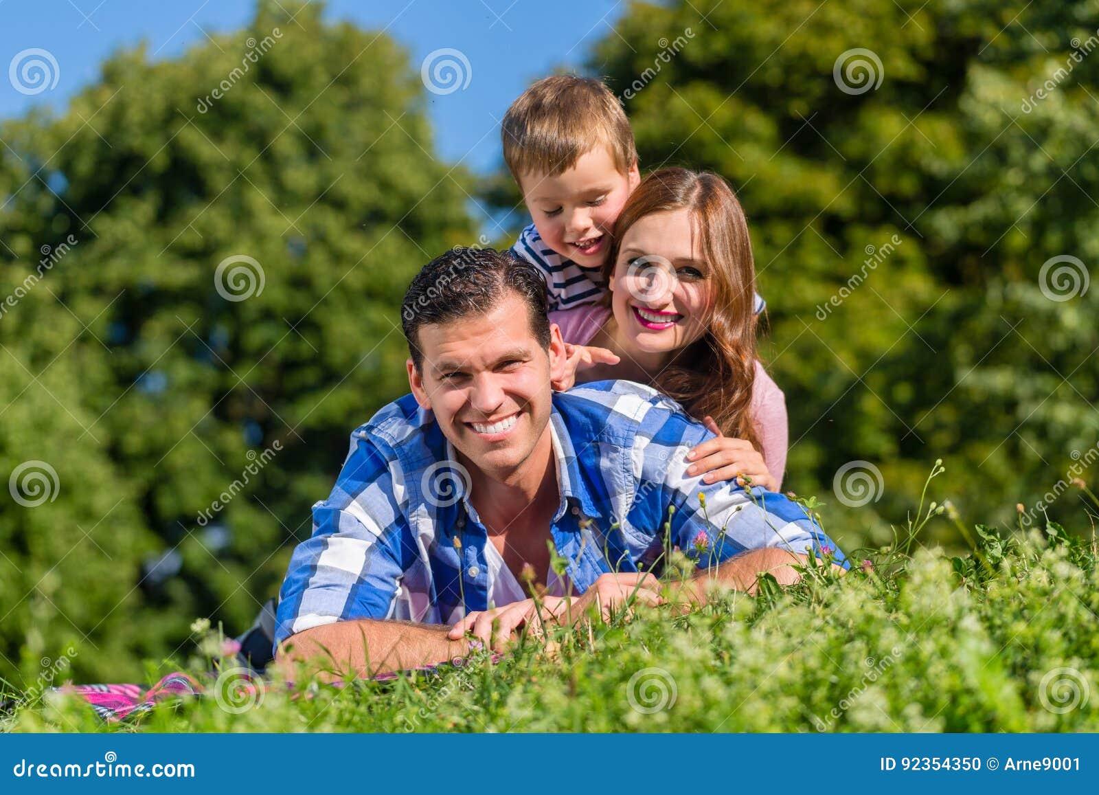 Familj som överst ligger i gräs av de