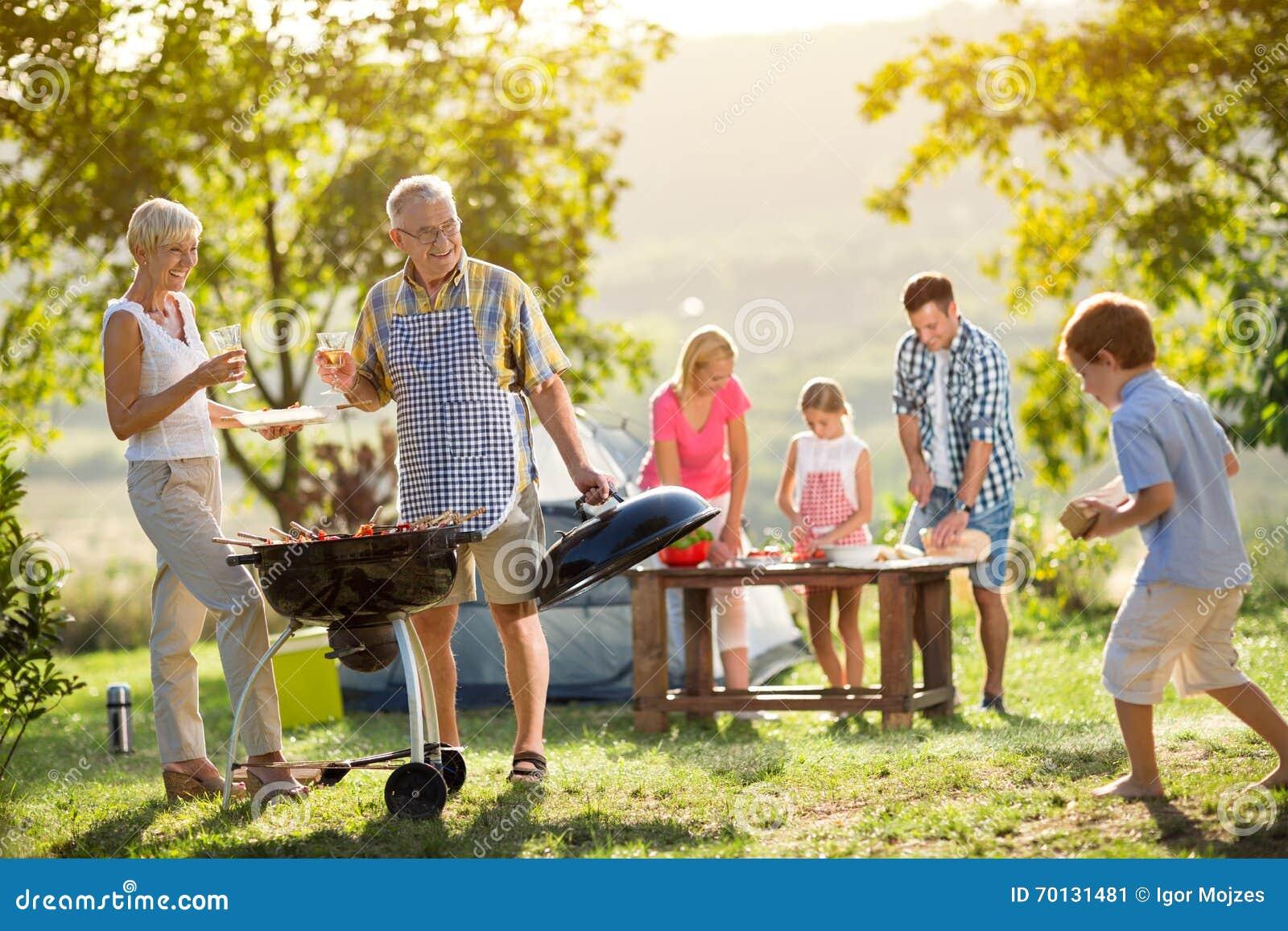 Familj som campar och lagar mat