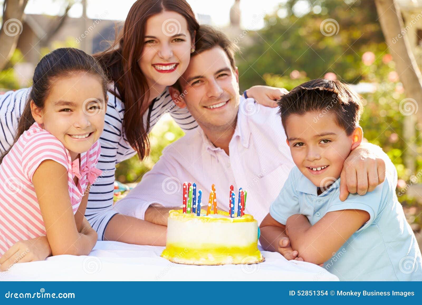 Familj som firar födelsedag utomhus med kakan