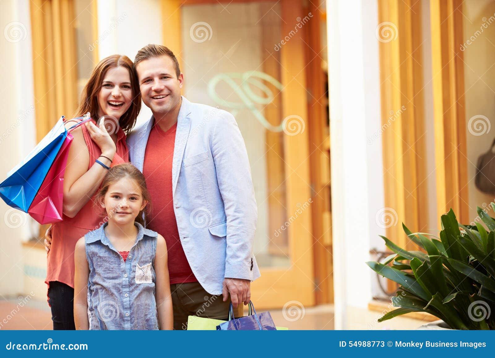 Familj som går till och med galleria med shoppingpåsar