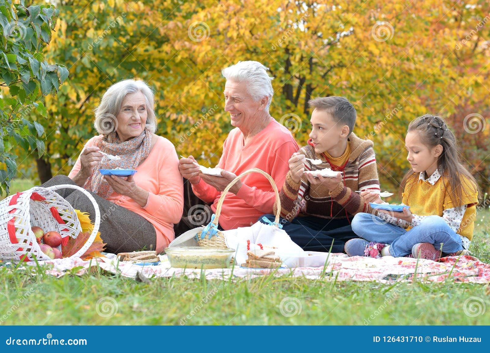 Familj som har en picknick i parkera