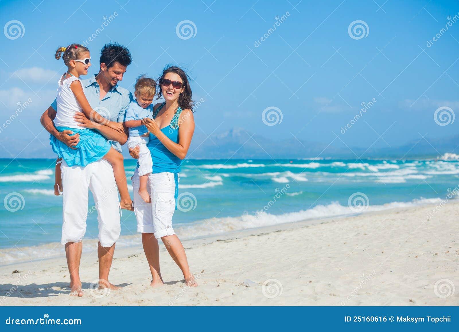 Familj som har gyckel på tropisk strand