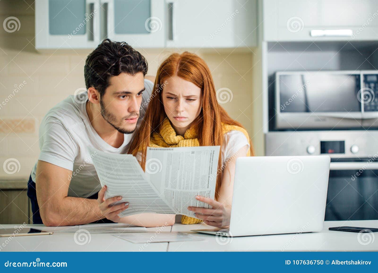 Familj som klarar av budgeten som granskar deras bankkonton genom att använda bärbara datorn i kök