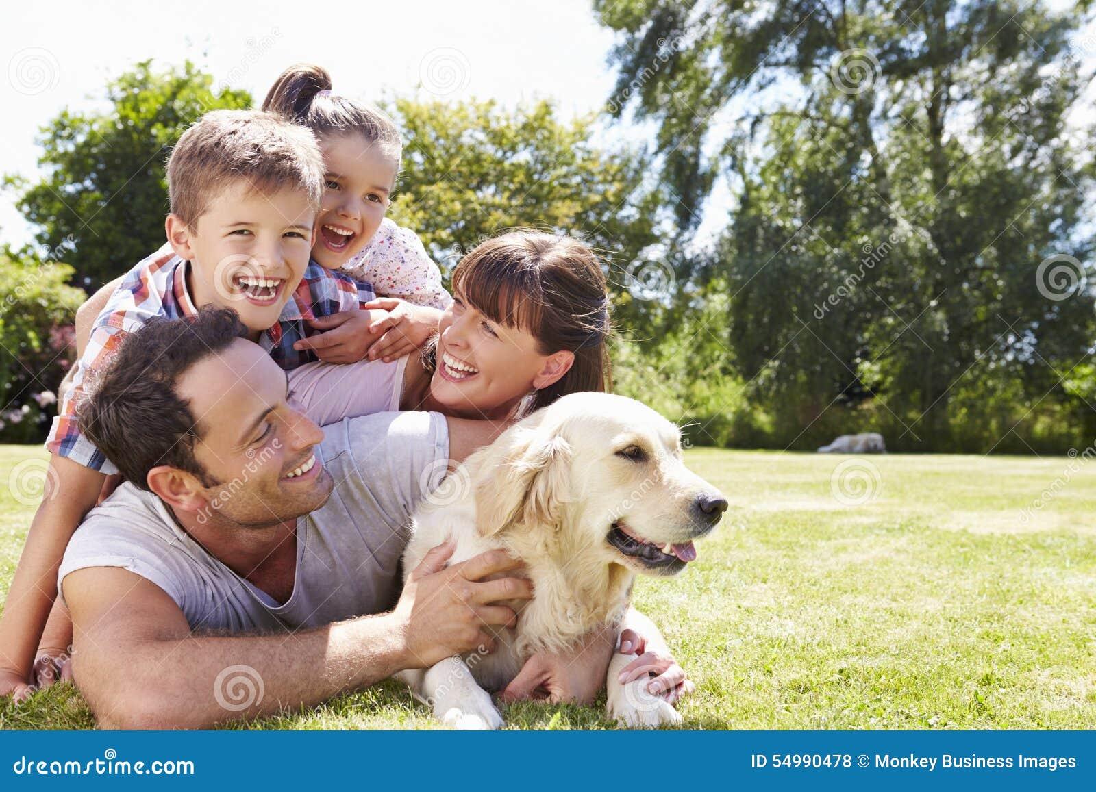 Familj som kopplar av i trädgård med den älsklings- hunden