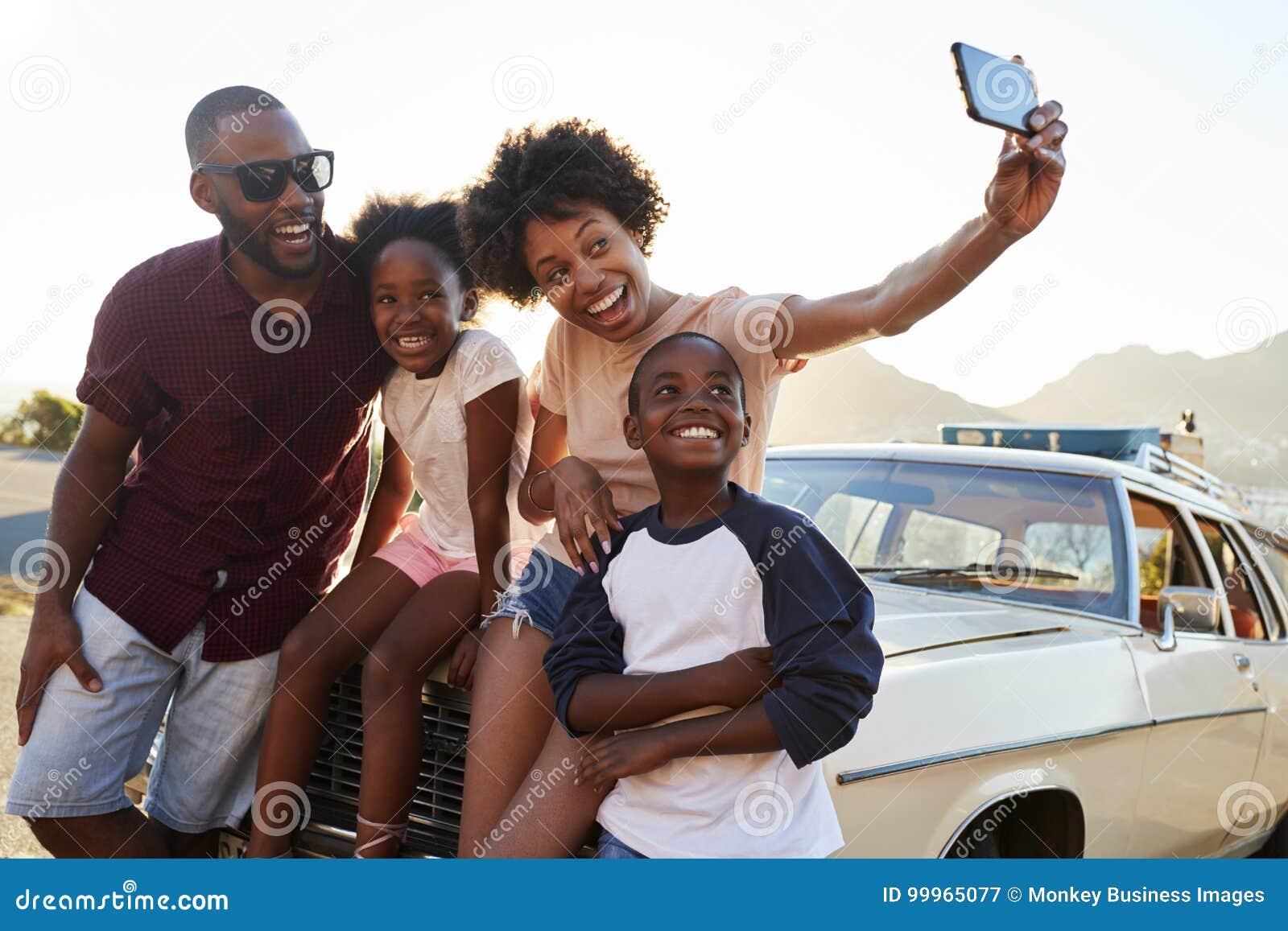 Familj som poserar för Selfie bredvid bilen som packas för vägtur