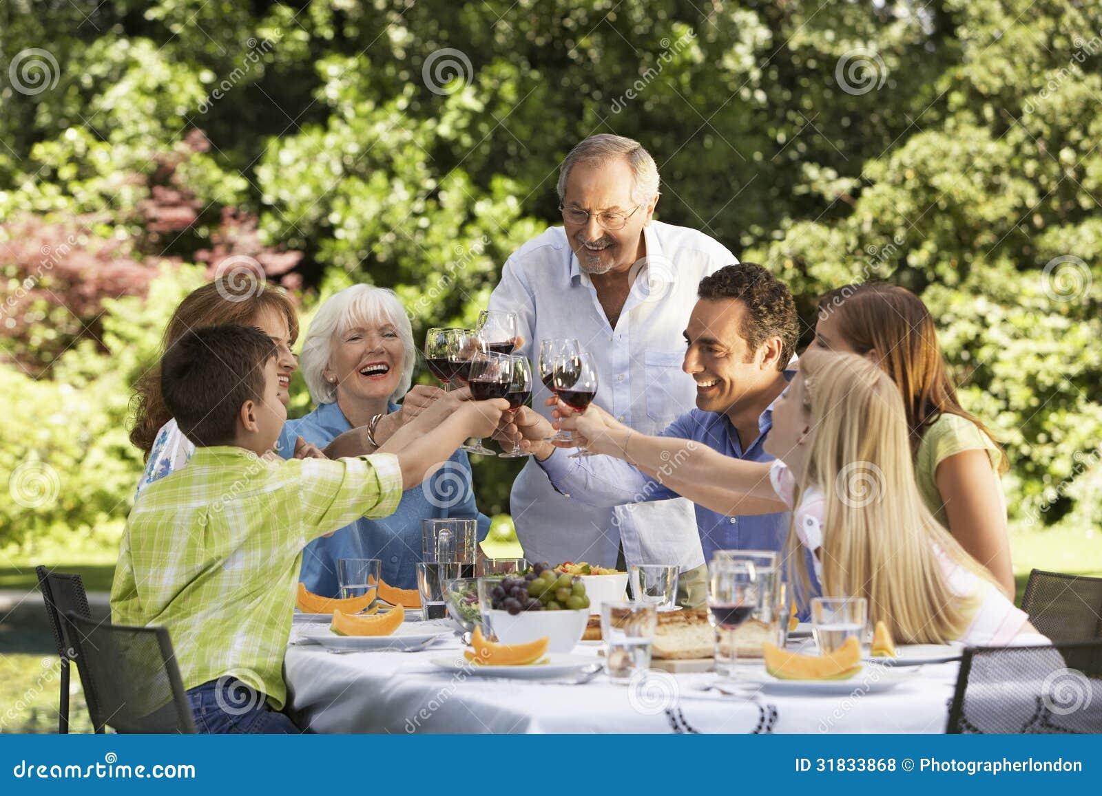 Familj som rostar vinexponeringsglas på tabellen i bakgård