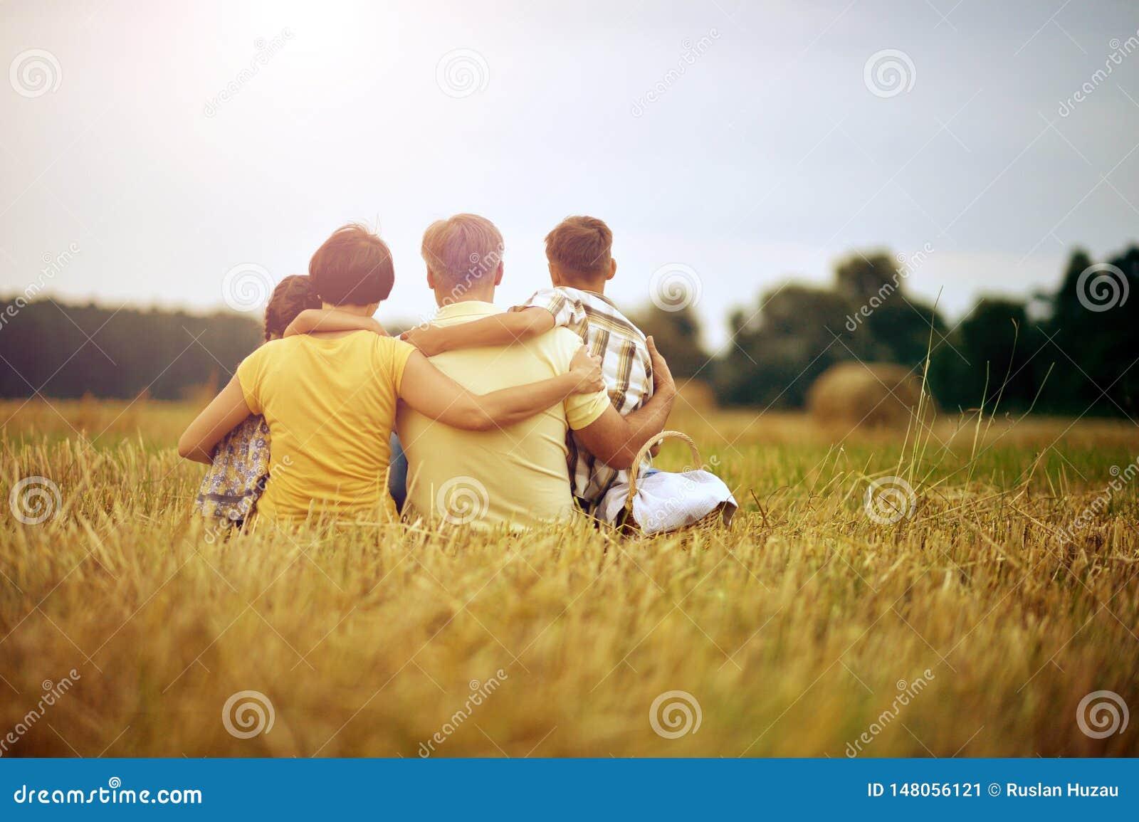 Familj som sitter på vetefält i solig dag