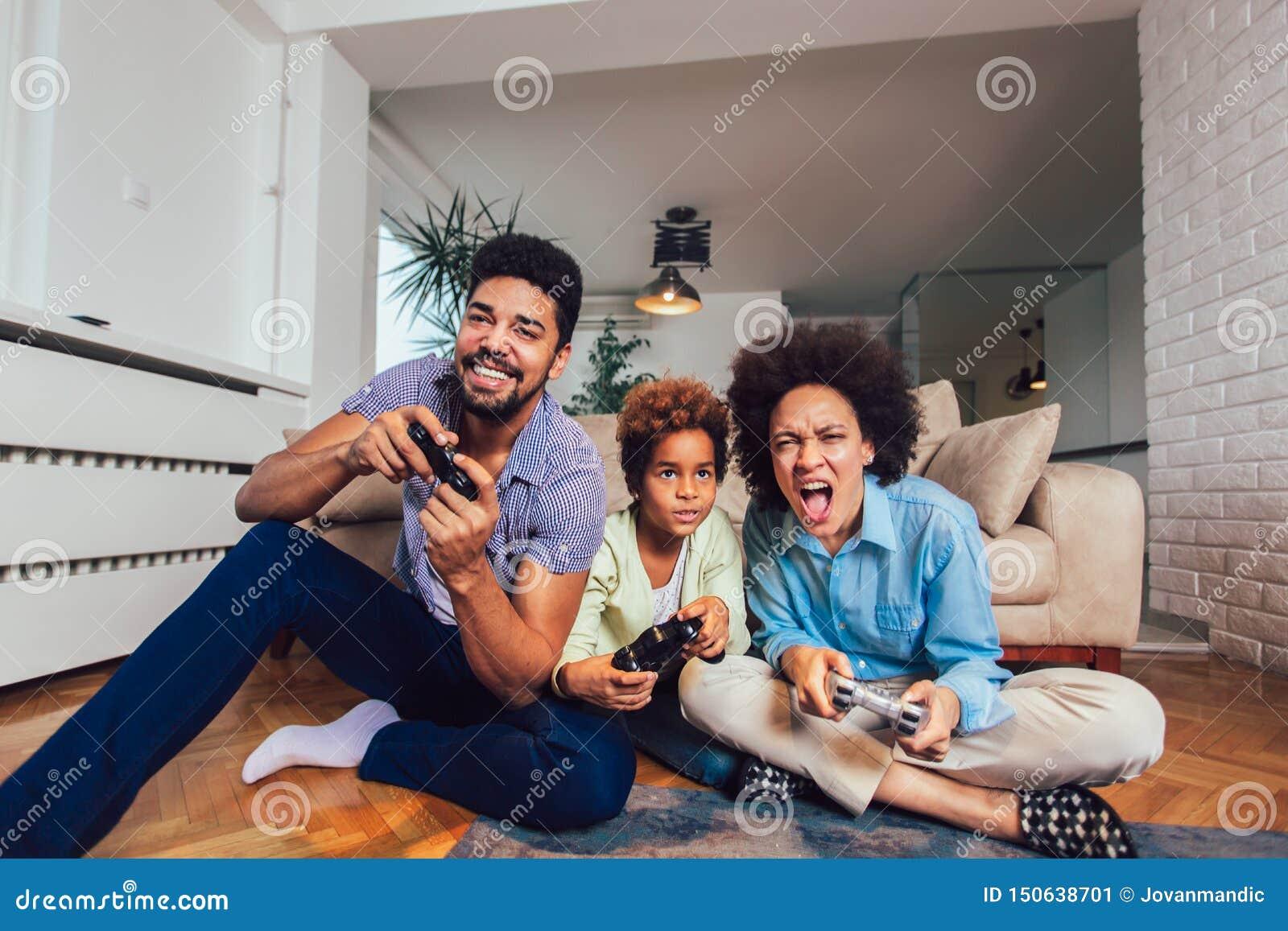 Familj som sitter p? soffan som spelar tillsammans videospel, selektiv fokus