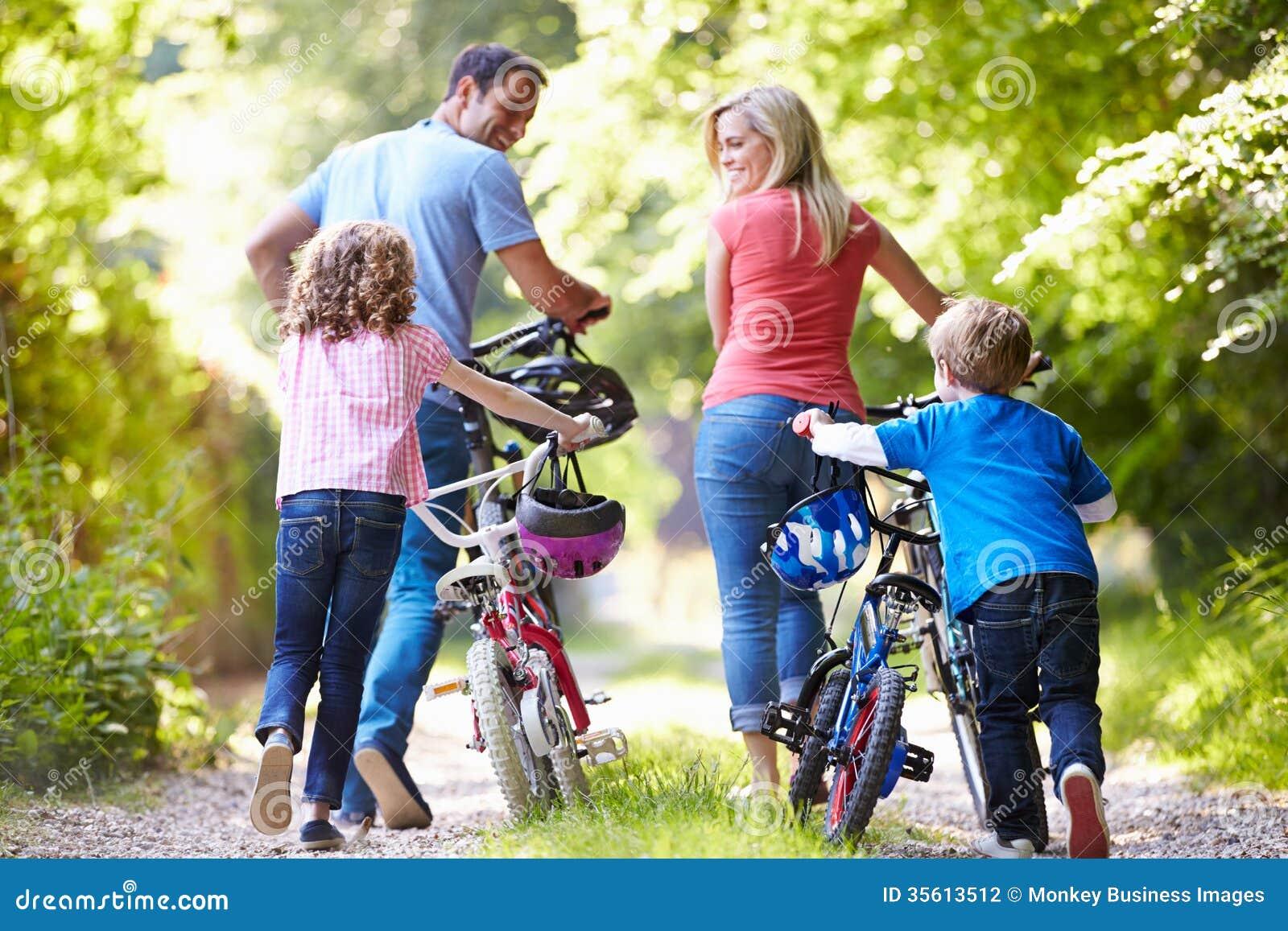 Familj som skjuter cyklar längs landsspår