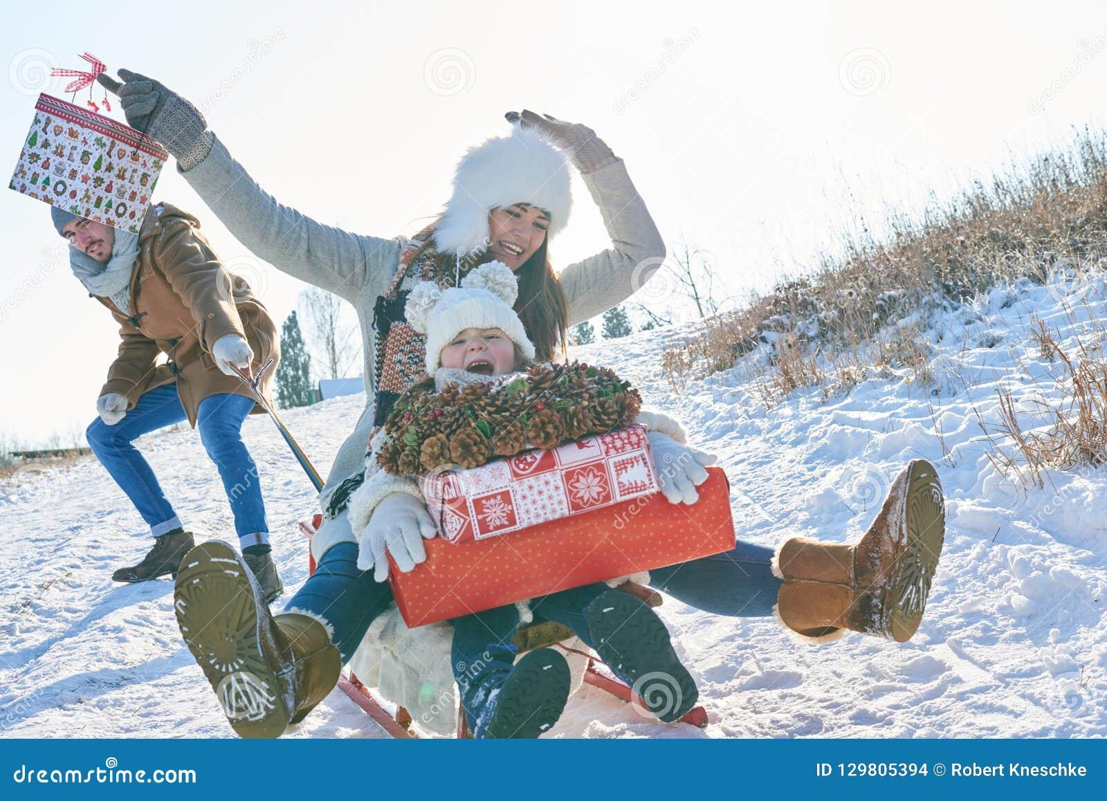 Familj som sledding i vinter med entusiasm