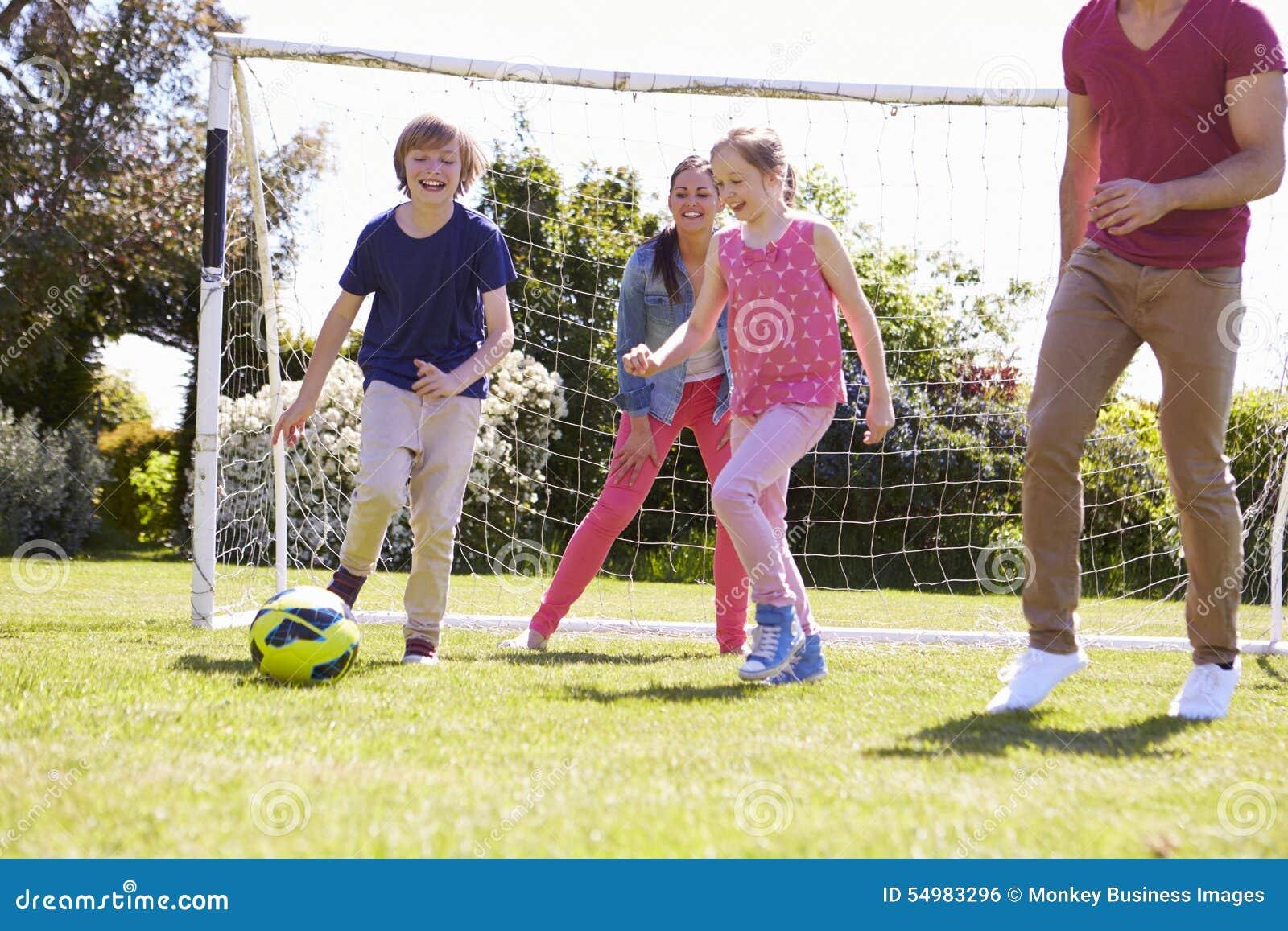 Familj som spelar fotboll tillsammans