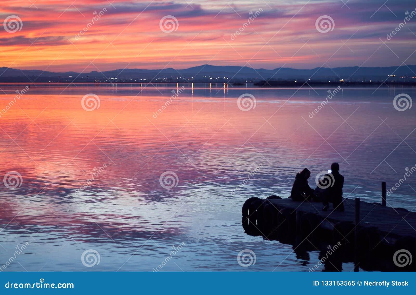 Familj som tar bilder i solnedgången av det lugna vattnet av Albuferaen de Valencia, Spanien