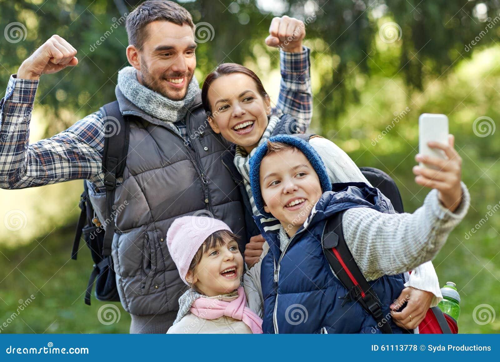 Familj som tar selfie med smartphonen i trän