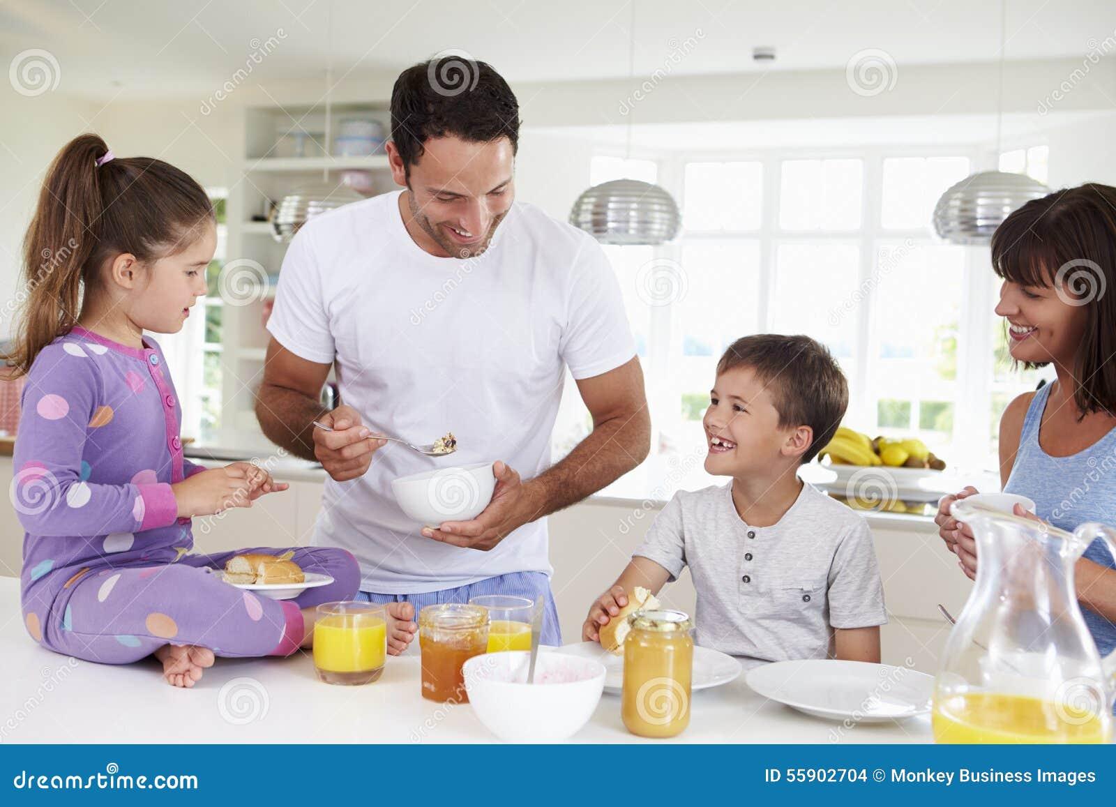 Familj som tillsammans äter frukosten i kök