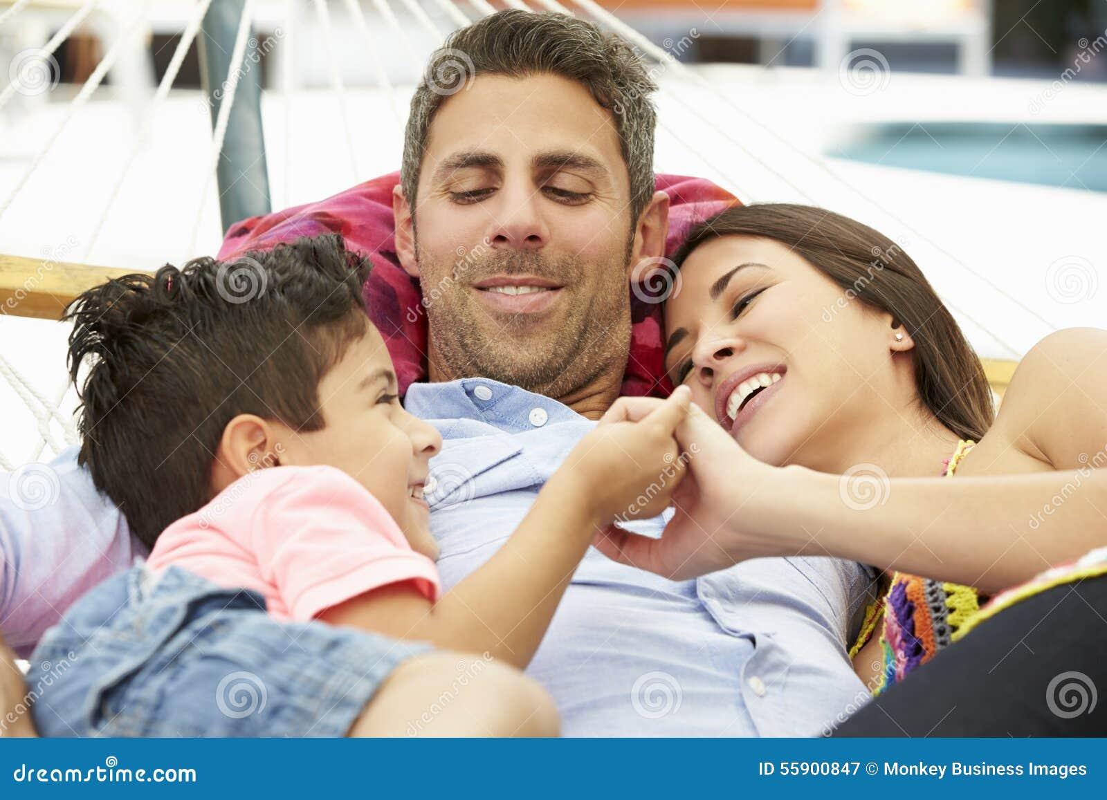 Familj som tillsammans kopplar av i trädgårds- hängmatta