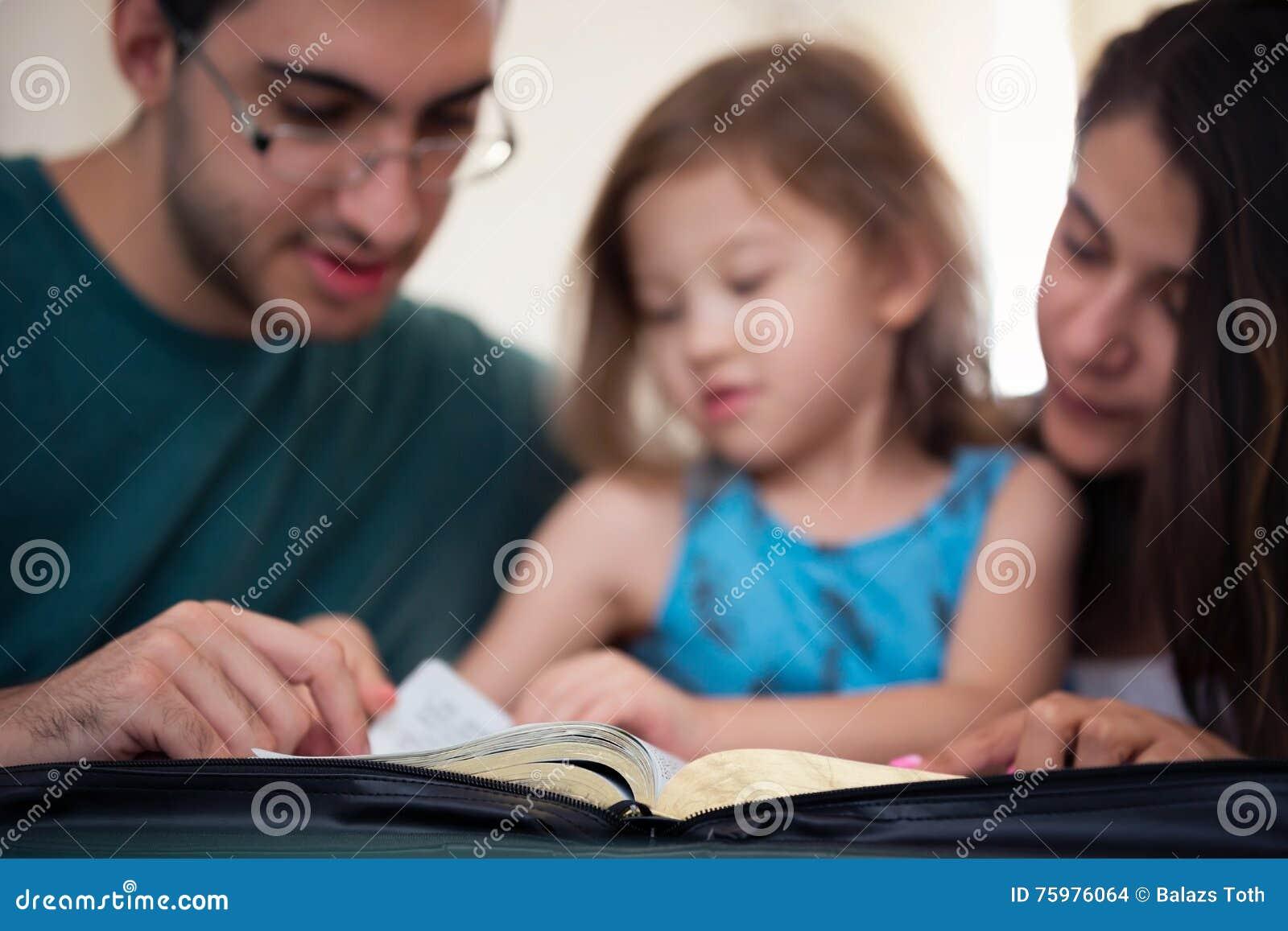 Familj som tillsammans läser bibeln