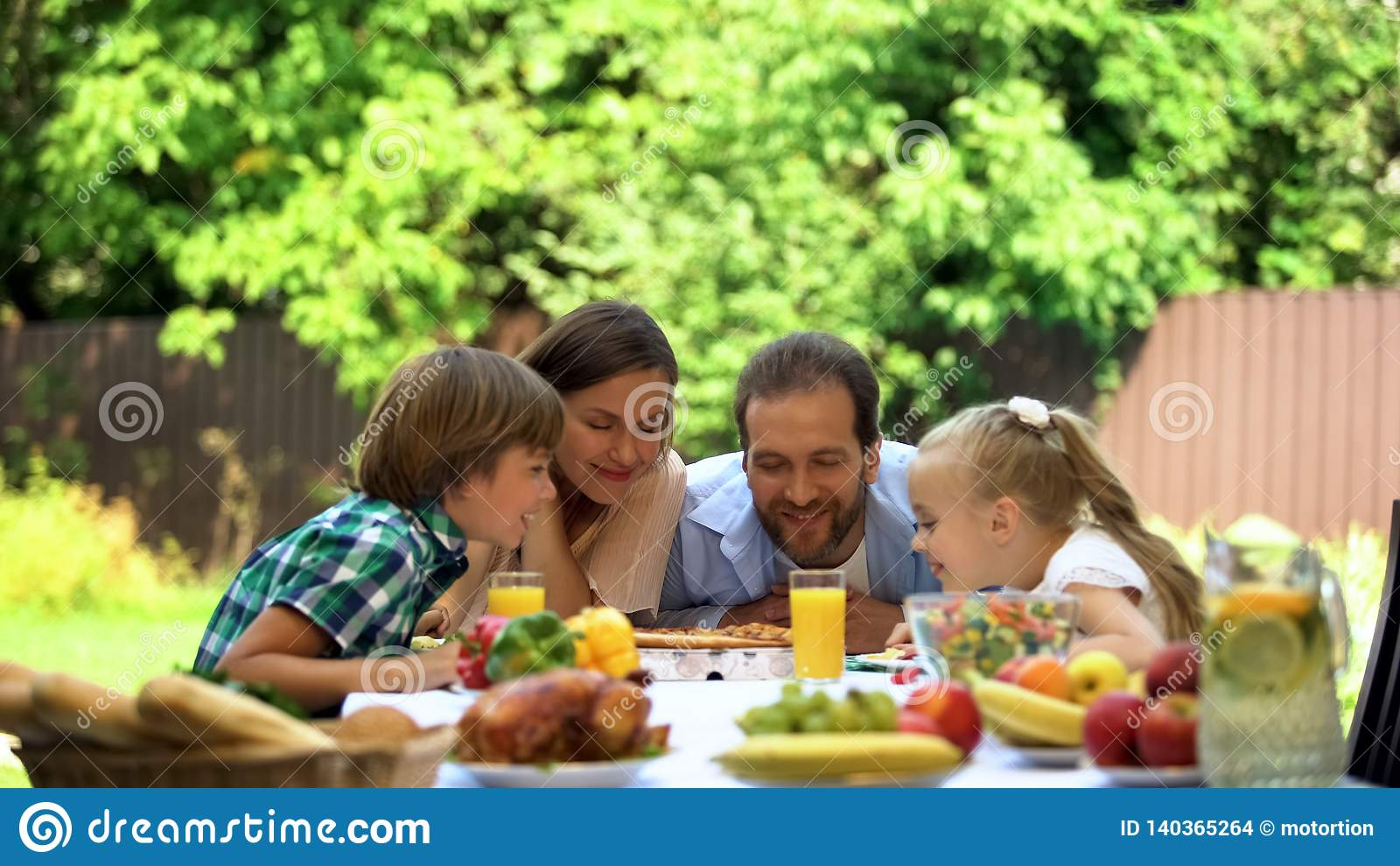 Familj som tycker om lukten av doftande pizza, italiensk kokkonst, mathemsändning