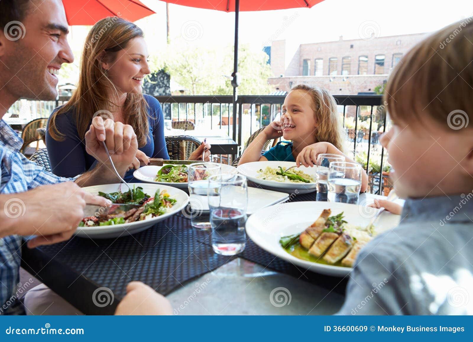 Familj som tycker om mål på den utomhus- restaurangen