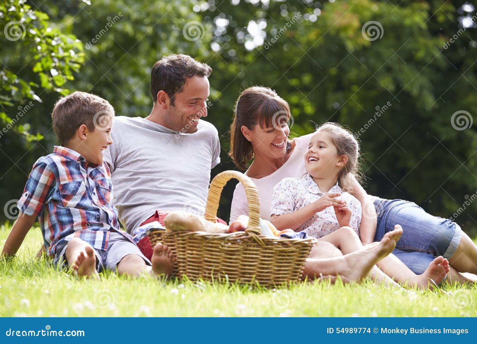 Familj som tycker om sommarpicknicken i bygd