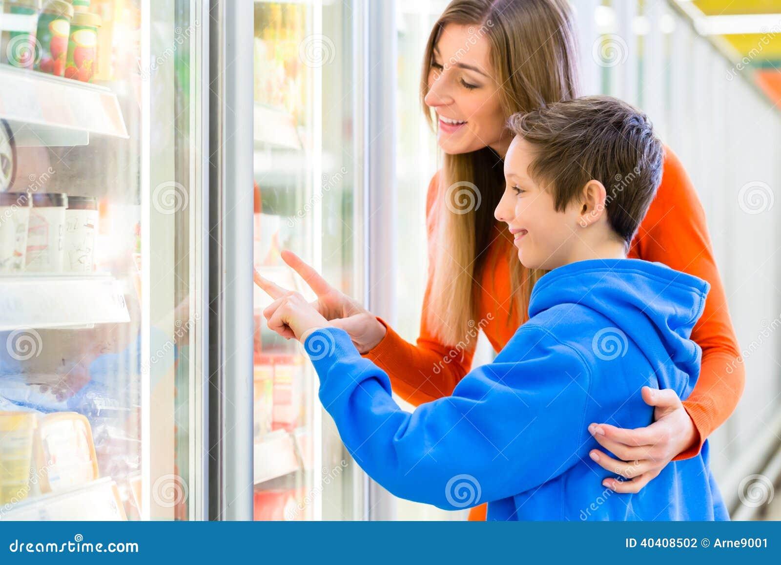 Familj som väljer kylde produkter i stormarknad