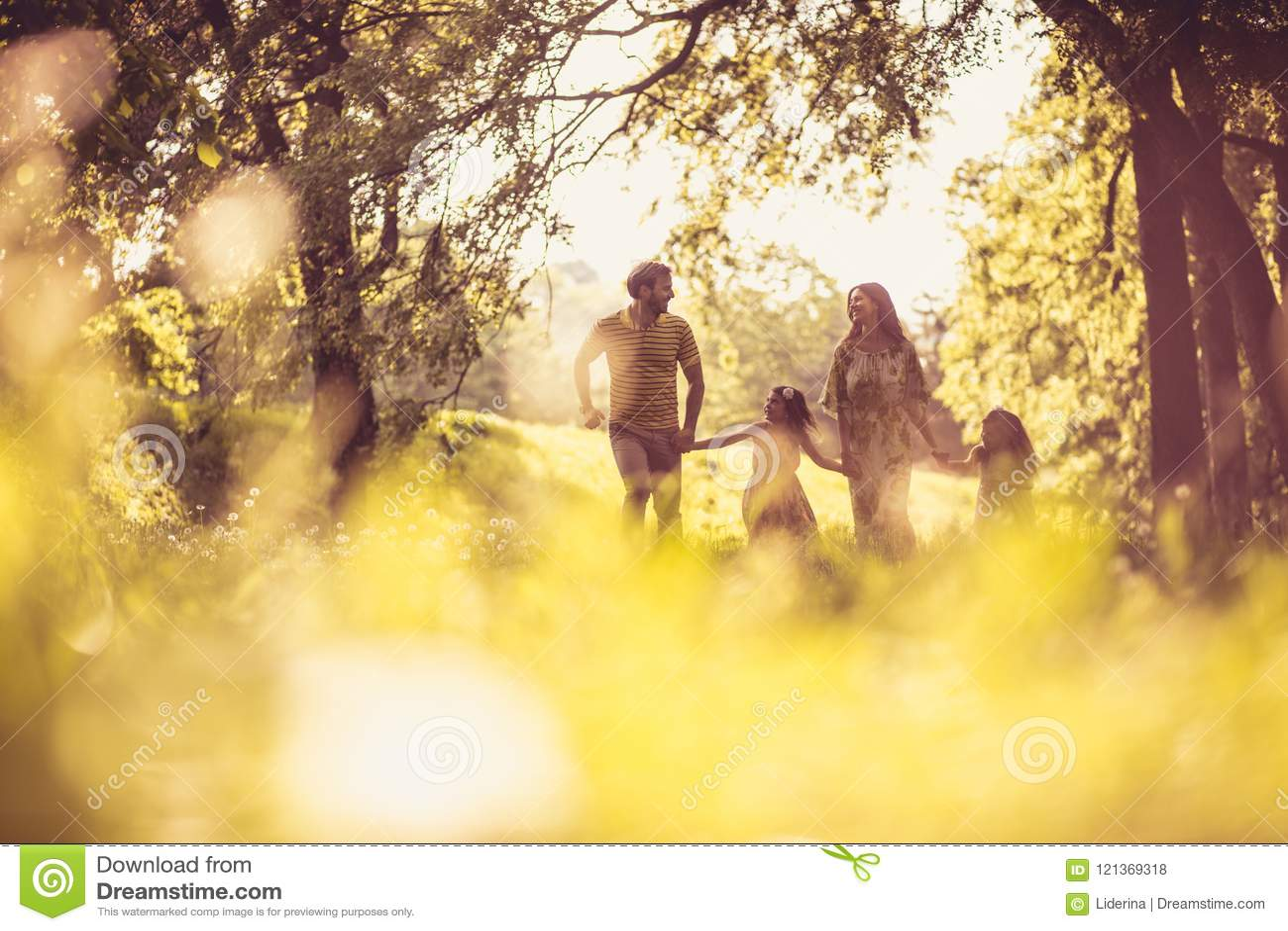 Familj Tid Lyckliga föräldrar med deras små flickor i natur