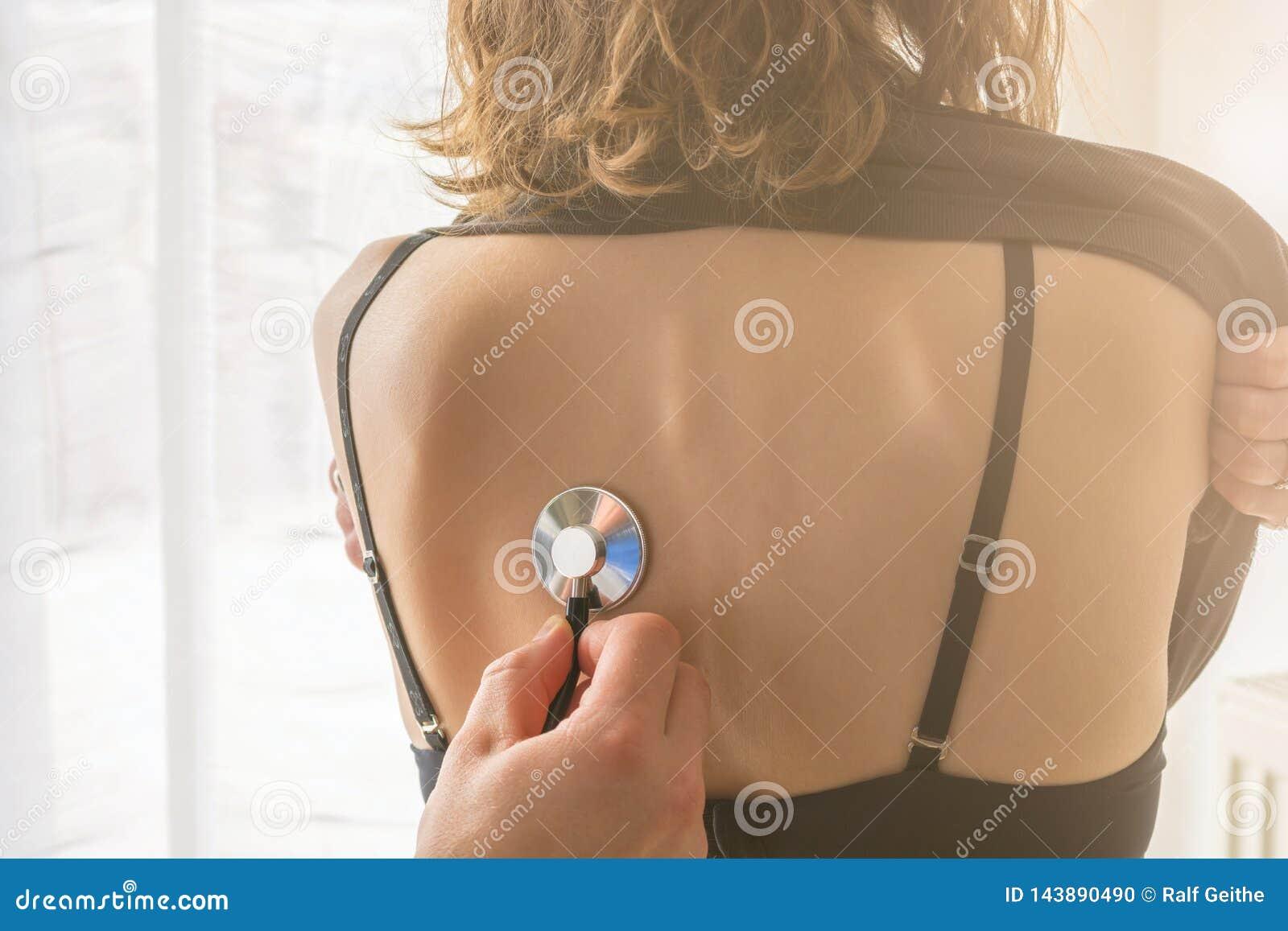 Familjdoktorn lyssnar till lungorna av en ung kvinna med stetoskopet