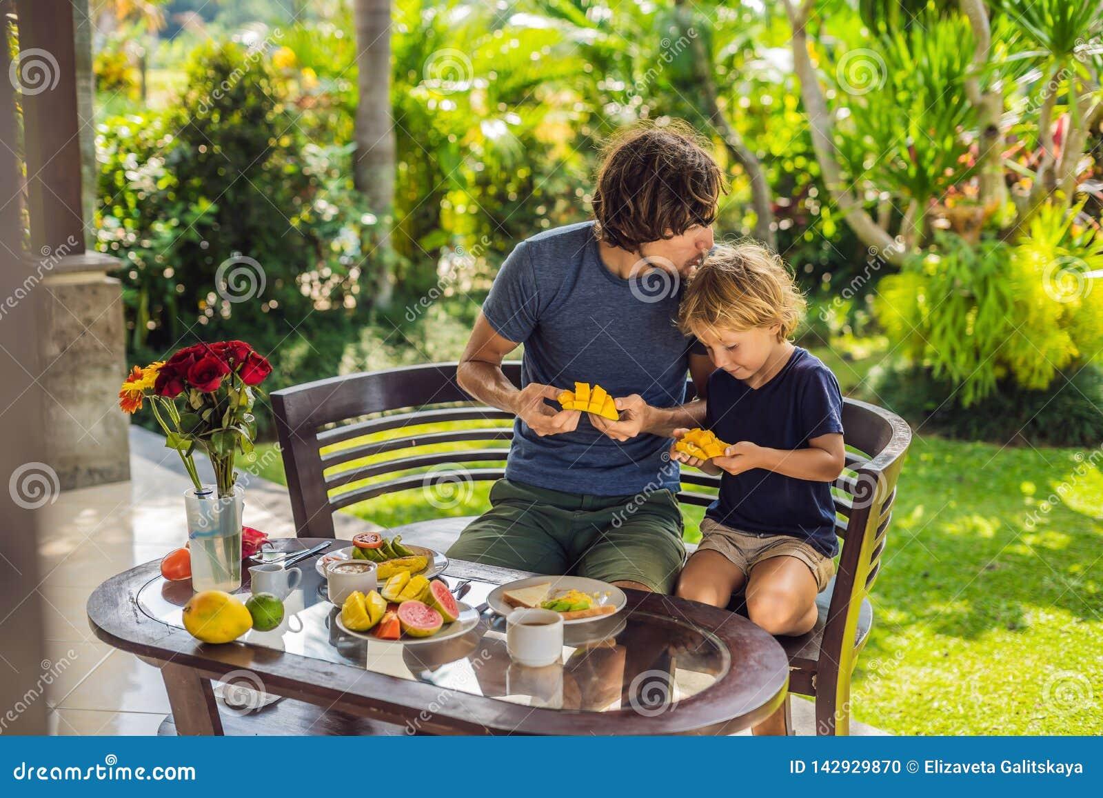 Familjen av två som utmärkt äter, tjänade som frukosten utanför den stiliga unga mannen som häller något kaffe och hans gulliga ä