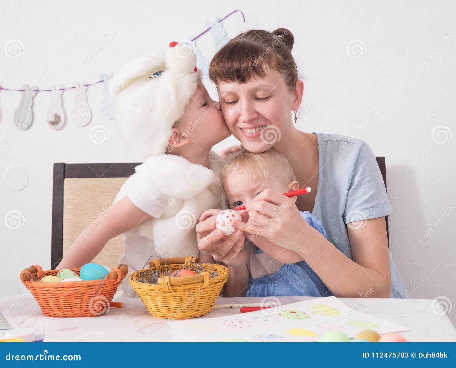 Familjen firar påskhögtiden: Mamman målar en modell på påskägget Sonen kysser hans moder på kinden