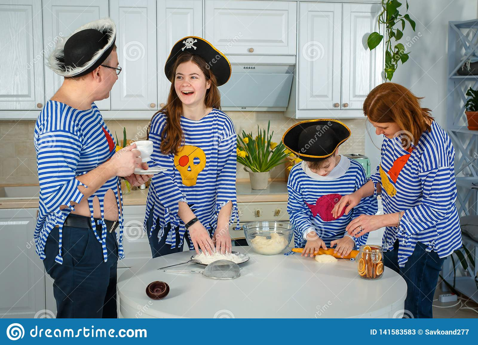 Familjen lagar mat tillsammans Make, fru och deras barn i köket Familjen knådar deg med mjöl