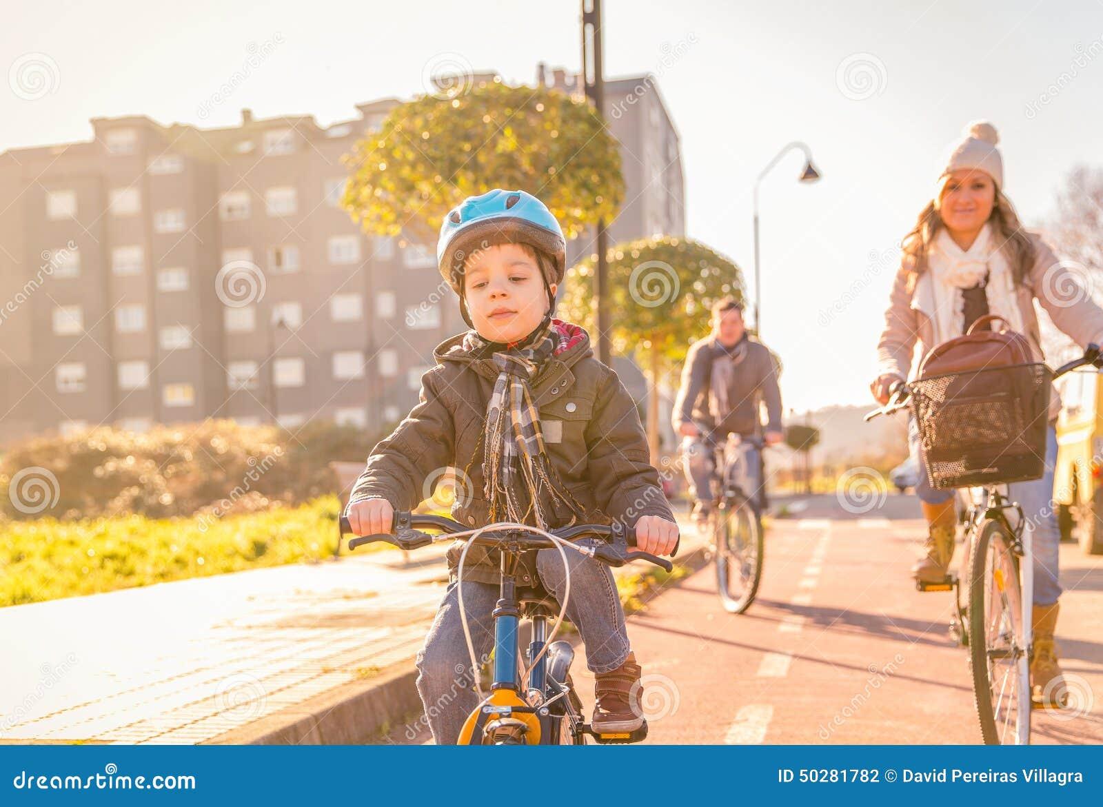 Familjen med barnridning cyklar i staden