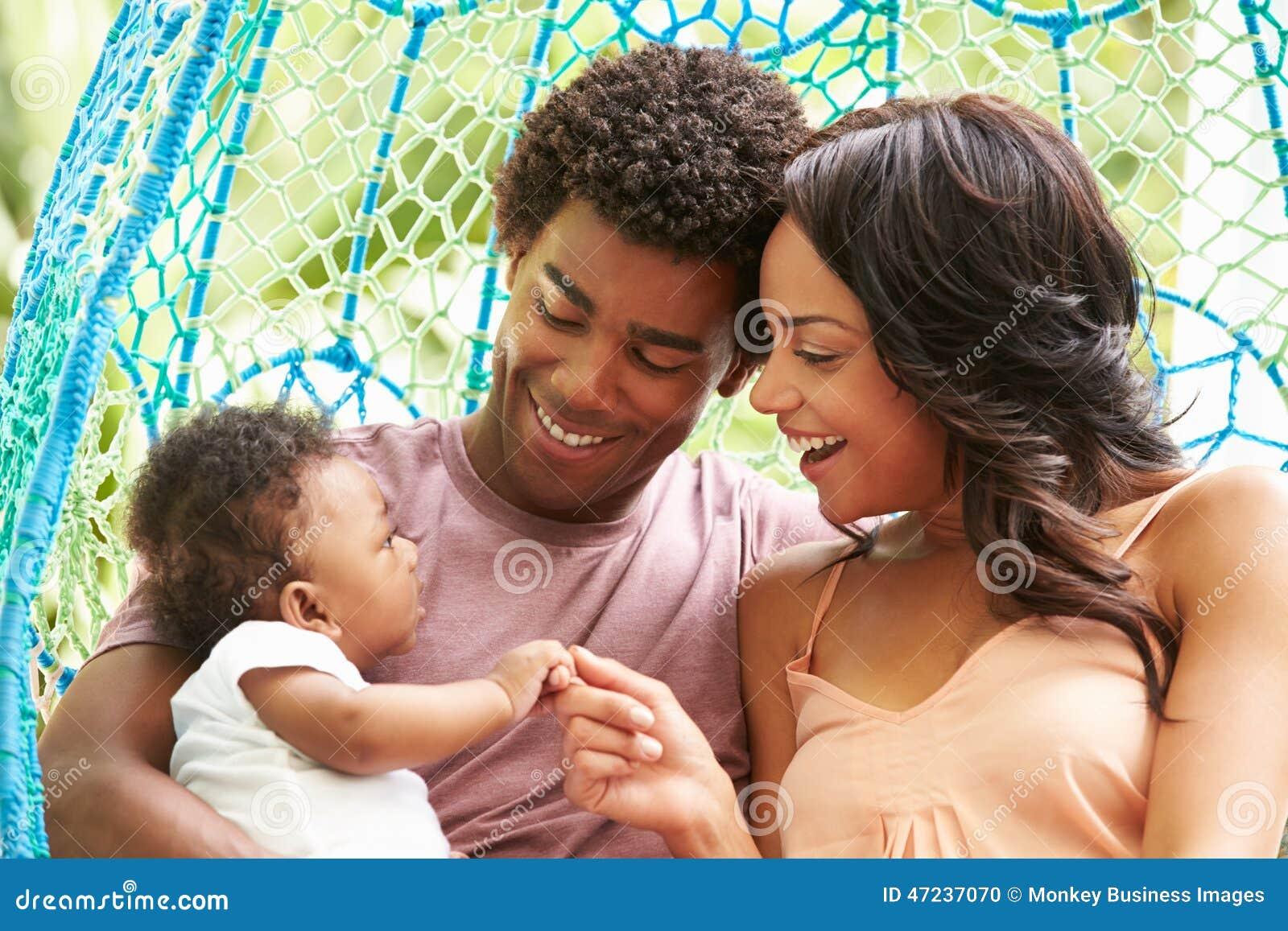 Familjen med behandla som ett barn att koppla av på utomhus- trädgårds- gunga Seat